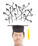 Confused graduate looking  direction arrow Stock Image