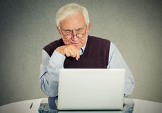 Confused grandfather using a pc. Closeup confused grandfather using a pc computer sitting at desk Stock Image