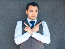 Confused guy pointing opposite fingers. Closeup portrait of young business man thinking, daydreaming,pointing opposite directions, looking confused,  gray Stock Photo