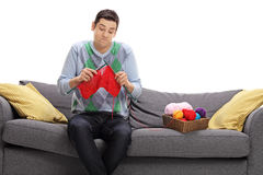 Confused guy sitting on a sofa and attempting to knit Royalty Free Stock Photos