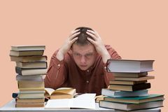 Confused guy sitting at a table with a pile of books isolated on a light background Stock Images