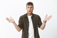 Confused handsome blond man with blue eyes raising hands sideways in dismay and clueless gesture being dumped. Unexpectedly standing questioned and disappointed stock image