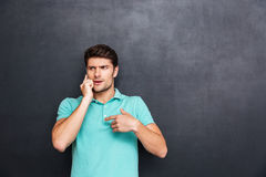 Confused handsome young man standing and talking on cell phone Stock Image