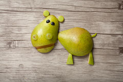 Confused hippo made of pear. On wooden background stock photography
