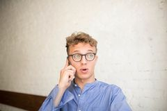 Confused hipster man talking via mobile phone, sitting in modern interior against brick wall. stock photography