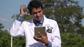 Confused hispanic doctor using tablet. A handsome adult hispanic man stock video footage