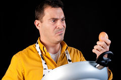 Confused househusband. The difficult combination of  pan and egg Royalty Free Stock Photos