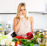 Confused housewife in the kitchen Stock Photography