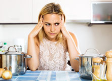 Confused housewife in the kitchen Royalty Free Stock Photo