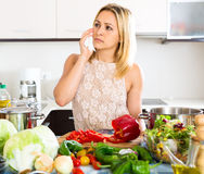 Confused housewife in the kitchen Royalty Free Stock Images