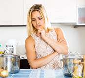 Confused housewife in the kitchen Stock Images