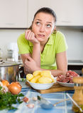 Confused housewife at kitchen Stock Images