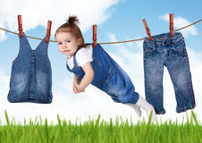 Confused housework creative concept, Funny child hanging on clot. Confused housework concept, Funny child hanging on clothesline Royalty Free Stock Photography