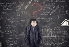 Confused kid and blackboard. With formula and red question mark, asking for solution Royalty Free Stock Photography
