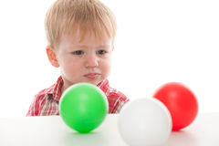 Confused kid looking at balls Royalty Free Stock Photography