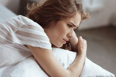 Confused lady thinking about her problem. What should I do. Worried woman lying on a bed and looking into vacancy while thinking about something serious Royalty Free Stock Photo