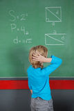 Confused Little Boy Looking At Board. Rear view of confused little boy looking at board in classroom Royalty Free Stock Photography
