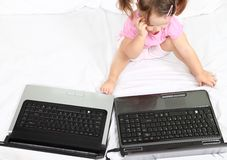 Confused little girl in front of two laptops Stock Photo
