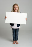 Confused little girl holding sign Stock Image