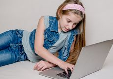 Confused little girl using a laptop Stock Photos