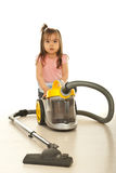 Confused little girl with vacuum cleaner Stock Image