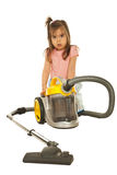 Confused little girl with vacuum cleaner. Confused little housewife behind a vacuum cleaner isolated on white background Stock Photography
