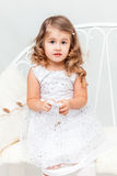 Confused little girl in white. Studio portrait Stock Photo
