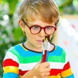 Confused little kid boy with glasses holding watercolors and brushes. Happy child and student is back to school stock photo