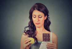 Confused looking woman with chocolate and apple trying to make a healthy choice Stock Images