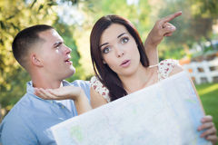 Confused and Lost Mixed Race Couple Looking Over Map Outside. Lost and Confused Mixed Race Couple Looking Over A Map Outside Together Royalty Free Stock Photos