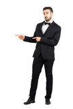 Confused luxurious man with bow tie pointing at copyspace. Stock Images