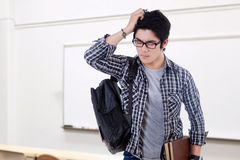 Confused male learner standing in class Stock Image
