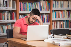 Confused Male Student Reading Many Books For Exam Stock Photography