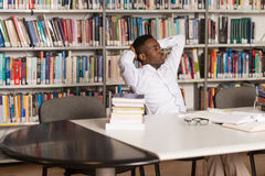 Confused Male Student Reading Many Books For Exam. Stressed African Student Of High School Sitting At The Library Desk - Shallow Depth Of Field Stock Image