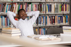 Confused Male Student Reading Many Books For Exam. Stressed African Student Of High School Sitting At The Library Desk - Shallow Depth Of Field Royalty Free Stock Images