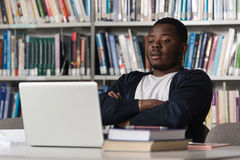 Confused Male Student Reading Many Books For Exam. Stressed African Student Of High School Sitting At The Library Desk - Shallow Depth Of Field Stock Photography