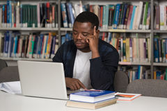 Confused Male Student Reading Many Books For Exam. Stressed African Student Of High School Sitting At The Library Desk - Shallow Depth Of Field Royalty Free Stock Photo