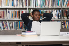 Confused Male Student Reading Many Books For Exam. Stressed African Student Of High School Sitting At The Library Desk - Shallow Depth Of Field Royalty Free Stock Photography