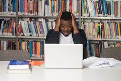 Confused Male Student Reading Many Books For Exam. Stressed African Student Of High School Sitting At The Library Desk - Shallow Depth Of Field Stock Photos