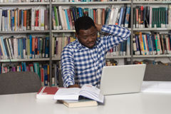Confused Male Student Reading Many Books For Exam. Stressed African Student Of High School Sitting At The Library Desk - Shallow Depth Of Field Stock Images