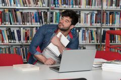 Confused Male Student Reading Many Books for Exam. Stressed Young Male Student Reading Textbook While Sitting in Library Royalty Free Stock Photography