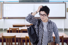 Confused male student standing in class. Portrait of male college student standing in the class and looks confused, carrying book and backpack Stock Photo