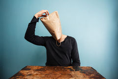 Confused man with bag over head. Sitting at a table Royalty Free Stock Photo