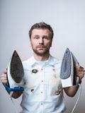 Confused man in burned shirt with two irons Stock Photo