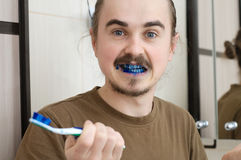Confused man about colored tooth brush Royalty Free Stock Image