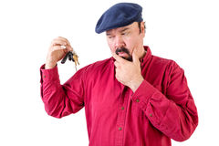 Confused man frowning at a bunch of car keys Stock Images