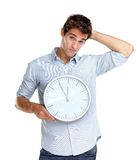 Confused man holding a clock Stock Image