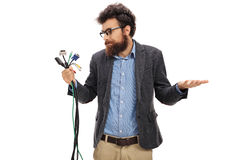Confused man holding different types of electronic connectors Royalty Free Stock Image