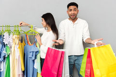 Confused man holding shopping bags while woman choosing clothes. Image of young confused men holding shopping bags while his women choosing clothes over grey stock photos
