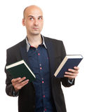 Confused man holding two books in hands Stock Photos